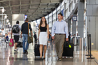 View of young couple holding suitcase luggage while walking through the Austin–Bergstrom International Airport (ABIA) terminal.
