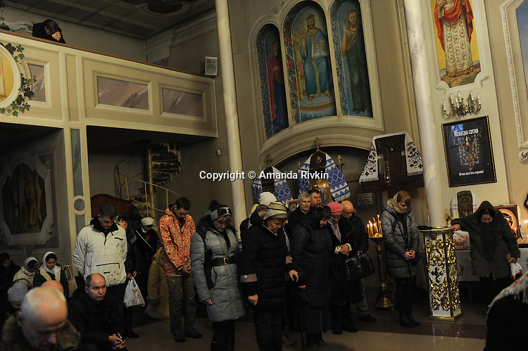 Parishioners bow and kneel during Christmas mass at the Christmas Church in Odessa, Ukraine on January 7, 2016.  Orthodox Christians around the world celebrate Christmas on January 7.