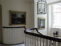 The curved balustrade at the top of the graceful staircases opens onto the landing