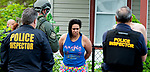 WATERBURY,  CT-051719JS14-  Officers detain residents from a home on East Liberty Street as they search the home as part of a city-wide operation on Friday. Waterbury Police, with cooperation State Police, Watertown Police, the States Attorney's Office, the DEA and ATF conducted search and seizures as well as searching for wanted suspects who police say were suspected in the sale of heroin.<br /> Jim Shannon Republican American