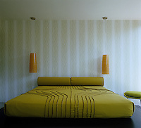 A pair of pendant lights hang on either side of the bed in this modern bedroom