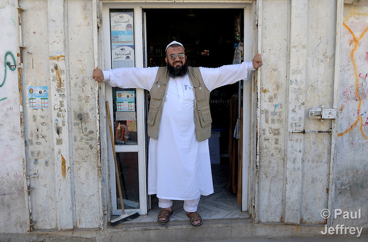 A shopkeeper stands in the doorway of his shop in the Palestinian village of Shuqba, in the West Bank.