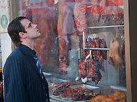 A man looks on meats on display through the window of a store in Toronto Chinatown April 23, 2010. Toronto Chinatown is an ethnic enclave in Downtown Toronto with a high concentration of ethnic Chinese residents and businesses extending along Dundas Street West and Spadina Avenue.