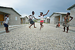 "Children jump rope in 2013 in a model resettlement village constructed by the Lutheran World Federation in Gressier, Haiti. The settlement houses 150 families who were left homeless by the 2010 earthquake, and represents an intentional effort to ""build back better,"" creating a sustainable and democratic community. Under ""informed consent"" rules that require prior approval, the photographer would have had to stop the girls from playing, have them identify their parents, explain the intricacies of ""informed consent"" and usage, get their signature, and then return to the street and photograph the girls at play. That's a process that's allegedly designed to assure that the girls are not depicted in an undignified manner. Photo by Paul Jeffrey."