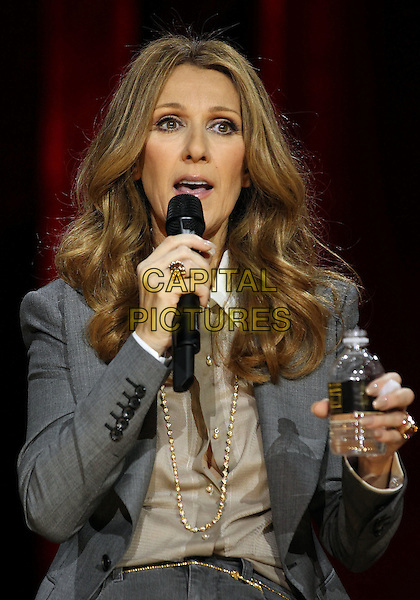 CELINE DION.Celine Dion's Momentous Return To The Colosseum Press Conference At Caesars Palace Resort Casino, Las Vegas, Nevada, USA..March 15th, 2011.half length grey gray jacket gold hand bottle water necklace beige shirt blouse microphone .CAP/ADM/MJT.© MJT/AdMedia/Capital Pictures.