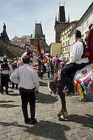 Participants at the ride of Kings in Prague with the Charles Bridge and the spectators as backdrop.<br /> <br /> Twelve-year-old Frantisek Libosvar dressed as a girl and with a rose in his mouth leads the royal procession during Ride of the Kings as part of Navalis Celebrations on May 15, 2015 in Prague, Czech Republic. The Navalis Saint John's celebrations take place to commemorate Czech saint and Prague native, Saint John of Nepomuk, patron of all people of the water. <br /> <br /> <br /> The Ride of the Kings takes place during the spring, as a part of the Pentecost traditions . A group of young men ride through a Prague in a ceremonial procession. The ride is headed by chanters, followed by pageboys with unsheathed sabres who guard the King &ndash; a young boy with his face partially covered, holding a rose in his mouth &ndash; and the rest of the royal cavalcade. The King and pageboys are dressed in women&rsquo;s ceremonial costumes, while the other riders are dressed as men. The entourage rides on decorated horses, stopping to chant short rhymes that comment humorously on the character and conduct of spectators. The chanters receive donations for their performance, placed either in a money box or directly into the riders&rsquo; boots. The King&rsquo;s retinue returns home after a few hours of riding, and celebrates in the evening at the house of the King with a small feast, music and dancing. The practices and responsibilities of the Ride of the Kings are transmitted from generation to generation. The traditional paper decorations for the horses and the ceremonial costumes, in particular, are made by women and girls familiar with the processes, colour patterns and shapes specific to each village.