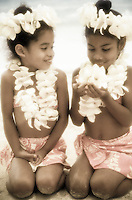 Two young girls with plumeria leis at the beach