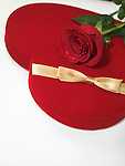 Red heart-shaped gift box and a red rose isolated on white background
