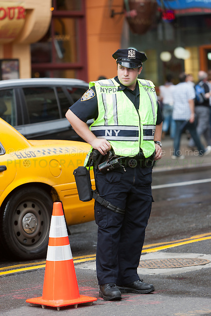 A NYPD police officer screens vehicles as they pass through a security checkpoint on 44th Street between 7th and 8th Avenues.
