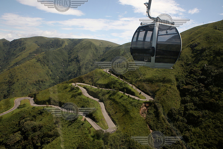 A cable car, that runs for over four kilometers from the base of Obudu Mountain to a resort at its summit, moves high above a winding road.