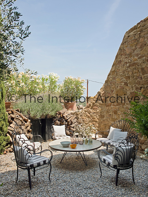 An outdoor seating area in the courtyard furnished with black wrought iron chairs
