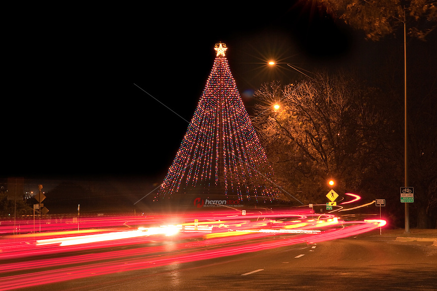 Barton Springs Road at night showing car headlight trails streaming across the Zilker Park Christmas Tree