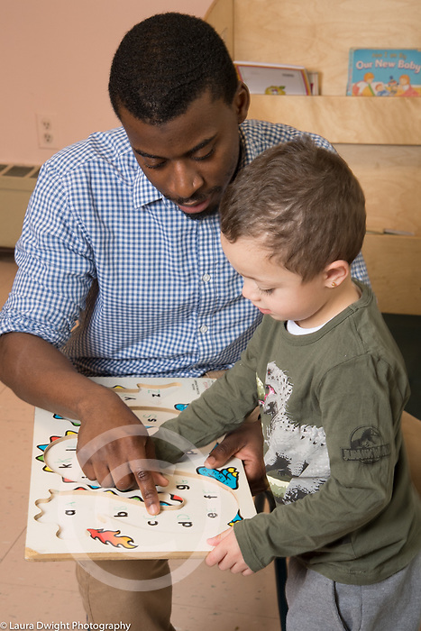 Education preschool 3 year olds male teacher with boy looking at alphabet puzzle talking and pointing at letters