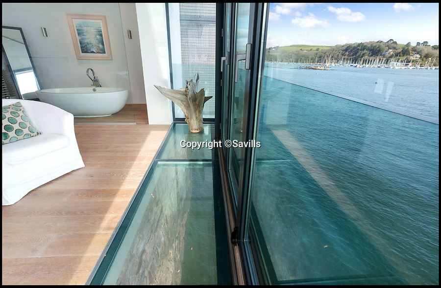 BNPS.co.uk (01202 558833)<br /> Pic: Savills/BNPS<br /> <br /> Glass floor in the master bedroom...<br /> <br /> An award-winning waterfront home that has spectacular seaside views has gone on the market for £5m.<br /> <br /> The aptly named River House sits right on the Dart Estuary in Devon and has been so cleverly designed there is a glass floor in the master bedroom that looks down on the water.<br /> <br /> Its main living areas have floor-to-ceiling bi-fold doors and glass Juliet balconies to give the property a feel of Venice rather than Devon.<br /> <br /> Interestingly, the five bedroom house is being sold along with a nearby two bedroom town house that is owned by the same vendors.