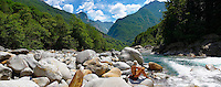 young lady sunbathing by a  rocky alpine foothills stream in the remote valley of Val Verzasca, near lavertezzo , Ticino