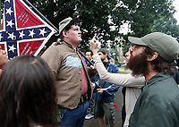 Charlottesville residents confronts Allen Armentrout of North Carolina who stood wearing a Confederate outfit with 2 guns in an effort to protect the Lee Statue Tuesday, Aug. 15, 2017 at Emancipation Park in Charlottesville, Va. The small crowd of Charlottesville residents protested him for 30 minutes before Police escorted Armentrout away from the park. Photo/Andrew Shurtleff