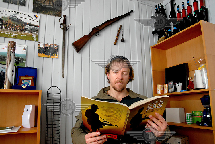 David Morales, former Spanish Army soldier, established a private security company called UC (Under Cover) Global in Spain, now he is a contractor. Pictured pictured at his home reading a book about the SAS with guns on display behinf him in La Linea de la Concepcion, Andalucia.