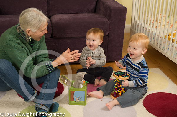 20 month old toddler fraternal twin boys with grandmother, playing with jack in the box toy, clapping when it opens, child care, grandmother takes care of grandchildren twice a week