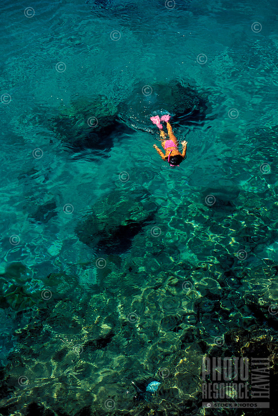 A girl snorkels at the clear waters off Black Rock, Kaanapali Beach, Maui with matching pink swimsuit snorkel, mask, and fins.
