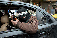 A member of the Free Syrian Army, an armed group that has risen up against the regime of President Bashar al-Assad, holding an AK47 as he travels in the back of a car in the Sakba district of Damascus. The Free Syrian Army claims to be predominately made up of deserters from the regular army who objected to being called on to shoot protesting civilians.
