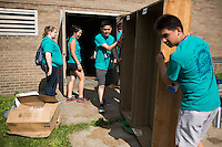 "Members move a bookshelf to a dumpster during ""Circle the City with Service,"" the Kiwanis Circle K International's 2015 Large Scale Service Project, on Wednesday, June 24, 2015, at the Friendship Westside Center for Excellence in Indianapolis. (Photo by James Brosher)"