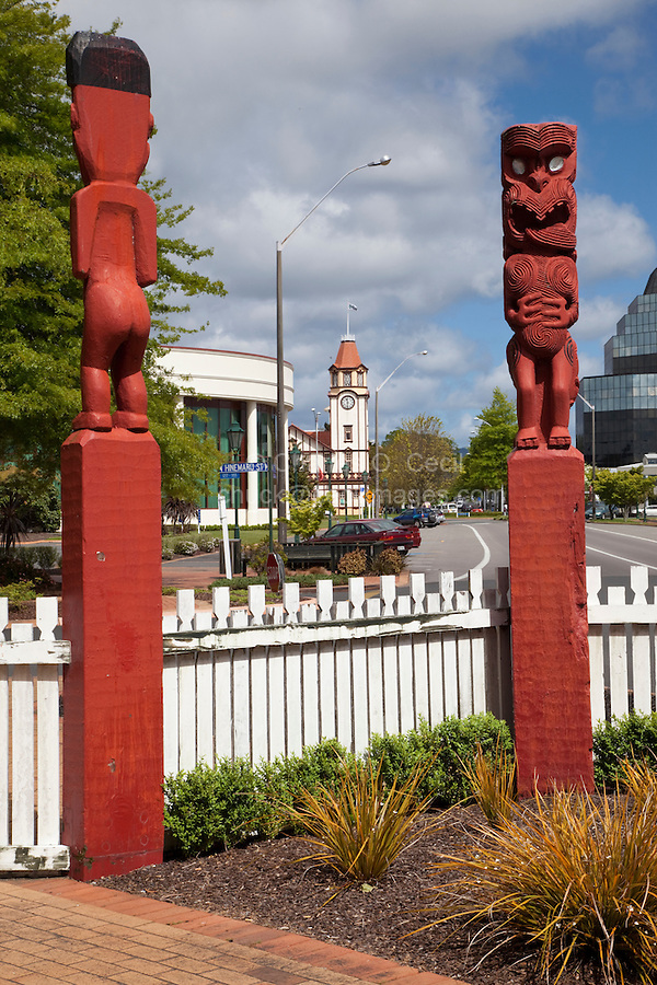 Rotorua, New Zealand.  Maori Totems at entrance to city park.  Town clock tower in distance.