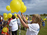 NWA Democrat-Gazette/BEN GOFF @NWABENGOFF<br /> Walkers prepare for a balloon release on Sunday Sept. 20, 2015 during the second annual Out of the Darkness Community Walk of Northwest Arkansas at Orchards Park in Bentonville. The fundraiser more than doubled in size this year, according to organizer Tyler West with the Arkansas Suicide Prevention Council, with 633 walkers raising $22,063 to help support suicide awareness and prevention efforts.