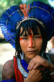 Altamira, Brazil. Ta'Kire Kayapo; warrior wearing bright blue feather headdress (cocar); Altamira Gathering, Para State, 1989.