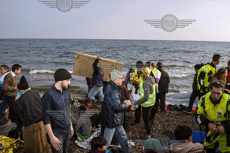 Aid workers, Greek recyclers, media and staff from the UNHCR organise a recent boat of refugees who have just landed.