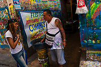 """José Corredor (""""Runner"""") talks with a girl while clearing paint from his brushes in the sign painting workshop in Cartagena, Colombia, 14 April 2018. Hidden in the dark, narrow alleys of Bazurto market, a group of dozen young men gathered around José Corredor (""""Runner""""), the master painter, produce every day hundreds of hand-painted posters. Although the vast majority of the production is designed for a cheap visual promotion of popular Champeta music parties, held every weekend around the city, Runner and his apprentices also create other graphic design artworks, based on brush lettering technique. Using simple brushes and bright paints, the artisanal workshop keeps the traditional sign painting art alive."""