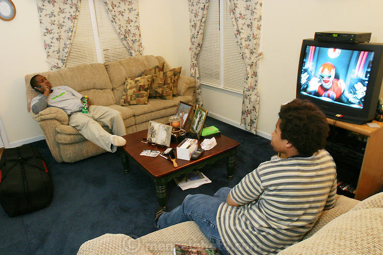 "(MODEL RELEASED IMAGE). Brandon and Tyrone (left) watch television, ""one of the downfalls,"" says Tyrone, ""to getting exercise. (Supporting image from the project Hungry Planet: What the World Eats.) The Revis family of Raleigh, North Carolina, is one of the thirty families featured, with a weeks' worth of food, in the book Hungry Planet: What the World Eats."