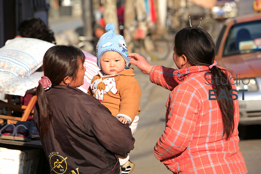 Shanghai, China - January 10: Two women and a baby chat on January 10, 2009 in Shanghai, China. (Photo by Lucas Schifres/Getty Images)