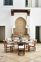 A round stone table is laid for an alfresco lunch on the courtyard patio. To one side, a decorative Moorish mosaic tiled panel is set behind a table.