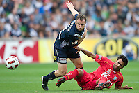 MELBOURNE, AUSTRALIA - JANUARY 09: Marcos Flores of United and  Grant Brebner of the Victory compete for the ball during the round 22 A-League match between the Melbourne Victory and Adelaide United at AAMI Park on January 9, 2011 in Melbourne, Australia. (Photo by Sydney Low / Asterisk Images)