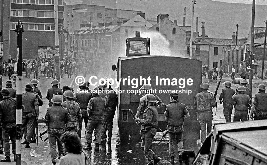 British soldiers use a water canon against rioters on the Lower Falls Road area of Belfast. The rioting broke out following a People's Democracy march was prevented by soldiers and police from entering the city centre in Belfast, N Ireland. The march was in support of PD leaders Michael Farrell and Tony Canavan who were on hunger strike seeking political status in Belfast's Crumlin Road Jail.  29 July 1973, 197307290522e<br /> <br /> Copyright Image from Victor Patterson, 54 Dorchester Park, <br /> Belfast, UK, BT9 6RJ<br /> <br /> t1: +44 28 9066 1296 (from Rep of Ireland 048 9066 1296)<br /> t2: +44 28 9002 2446 (from Rep of Ireland 048 9002 2446)<br /> m: +44 7802 353836<br /> <br /> e1: victorpatterson@me.com<br /> e2: victorpatterson@gmail.com<br /> www.victorpatterson.com<br /> <br /> Please see my Terms and Conditions of Use at www.victorpatterson.com. It is IMPORTANT that you familiarise yourself with them.<br /> <br /> Images used on the Internet must be visibly watermarked i.e. &copy; Victor Patterson<br /> within the body of the image and copyright metadata must not be deleted. Images <br /> used on the Internet have a size restriction of 4kbs and will be chargeable at current<br />  NUJ rates unless agreed otherwise.<br /> <br /> This image is only available for the use of the download recipient i.e. television station, newspaper, magazine, book publisher, etc, and must not be passed on to any third <br /> party. It is also downloaded on condition that each and every usage is notified within 7 days to victorpatterson@me.com<br /> <br /> The right of Victor Patterson to be identified as the author is asserted in accordance with The Copyright Designs And Patents Act (1988).