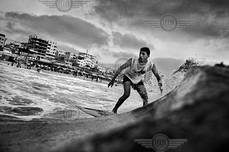 21 year old surfer Mahmoud Alyrashi rides a wave in the Mediterranean Sea off Gaza City. 'We want to show the world that we are not killers as they think, but we are peaceful people. When I surf I feel free, like a bird feels when it flies.'