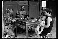 A Chinese woman holds her son as they sit together with bronze statues at the Mah-jong Museum in Ningbo of Zhejiang province in eastern China, September 2016.