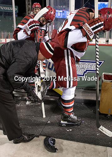 Ted Donato (Harvard - Head Coach) helps put on John Caldwell's (Harvard - 15) skateguards. - The Union College Dutchmen defeated the Harvard University Crimson 2-0 on Friday, January 13, 2012, at Fenway Park in Boston, Massachusetts.