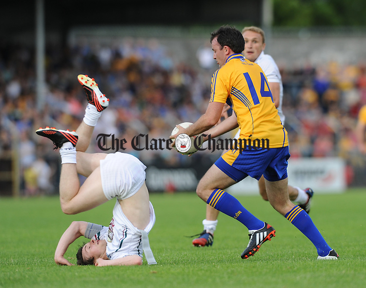 Ollie Lyons of Kildare in action against David Tubridy of Clare during their All-Ireland qualifier game in Ennis. Photograph by John Kelly.