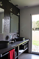 The walls and floor of this bathroom are of waxed  concrete painted an anthracite grey and storage on the open shelving beneath the double wash basins is provided by a pair of black suitcases