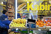 Switzerland. Geneva. Paquis neighborhood. Two police officers buy food in Kabir's shop on the Berne street.  21.03.12 © 2012 Didier Ruef..
