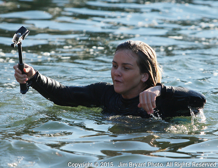Mariah Kipperberg swims a shore after  filming herself  jumping into the Burley Lagoon during the 31st annual Polar Bear on January 1, 2015 in Olalla, Washington. Over 500 hardy participants joined in on the annual New Year's Day Tradition by jumping into the chilly lagoon waters during the annual Polar Bear Plunge.