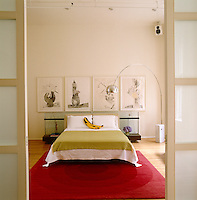 An elegant bedroom is seen through double sliding doors and has an intriguing collection of framed prints hanging above the bed