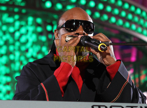 STEVIE WONDER .The Holiday Tree Lighting At L.A. Live & Opening Of L.A. Kings Holiday Ice held At L.A Live,  Los Angeles, CA, USA, .4th December 2010..music concert live on stage gig portrait headshot  sunglasses black red microphone polo neck harmonica .CAP/ADM/KB.©Kevan Brooks/AdMedia/Capital Pictures.