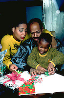 African American parents age 40 helping son age 6 wrap Christmas gifts.  St Paul Minnesota USA