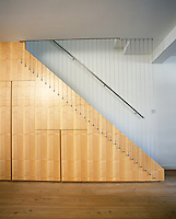 A side view of a modern wooden staircase lined with a wire banister.