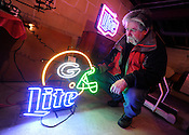 Tim Sczesny, of Milwaukee, examines a Green Bay Packers Miller Light neon light at a Mequon estate sale at 1311 W. El Rancho Dr. on Friday, Feb. 4, 201. Sczesny did not buy the light, but ended up paying $60 for an old concertina he found at the small ranch home. Ernie Mastroianni photo for the Milwaukee Journal Sentinel