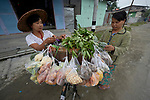A woman sells produce to another woman off her bicycle in Kalay, a town in Myanmar.