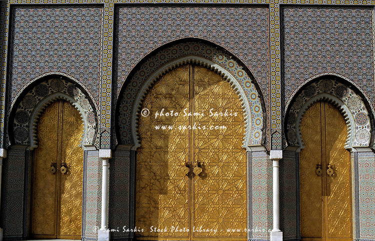 Three golden doors forming the grand entrance to the Royal Palace in Fez, Morocco.