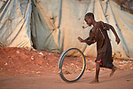 A girl rolls part of a truck wheel through the Yida refugee camp in South Sudan. Some 53,000 refugees from Sudan's Nuba Mountains live in the camp, with an equal number living in two nearby camps.